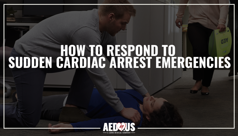 Woman laying unconscious and a man with his hands on her shoulders. Woman running in the background to bring an AED.