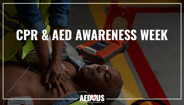 Woman performing CPR on man on the ground with G5 AED next to him.